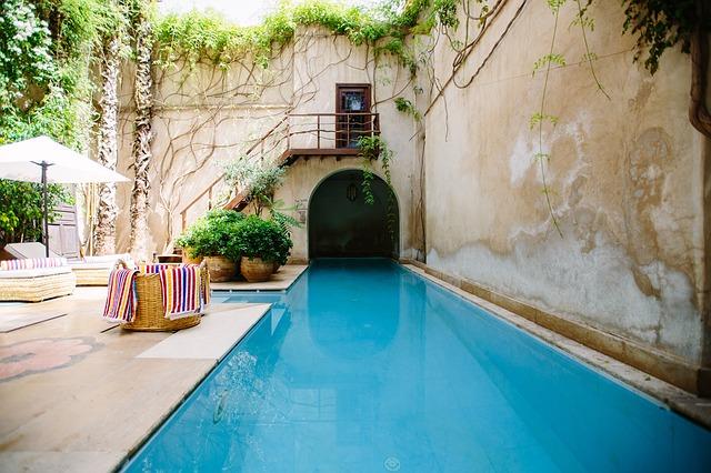 Dom s veľkým bazénom a chodmi na jeho vonkajšej časti.jpg